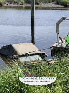 Recovery boat next to sunken boat