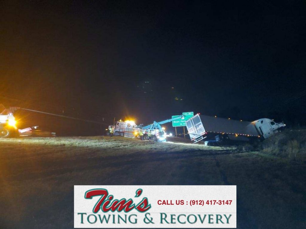 heavy wrecker provides heavy truck towing service to semi in ditch